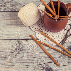 Wooden hooks for knitting, a round tangle of cotton yarn, an openwork napkin, a clay mug and old scissors on a gray wooden table. Toned photo.