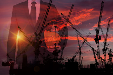 Concept image of Silhouette the building under construction with crane and Business man