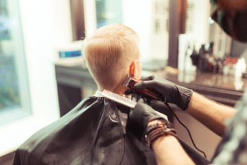 Handsome hairdresser cutting hair of male client. Men hairstylist serving client at vintage barber shop.