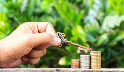 Hand held keys and coins.Business success concept.