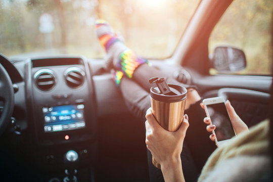 Autumn, Auto travel. Cose-up of a woman drinking take away cup coffee during the road trip in a car. Woman feet in warm socks on car dashboard. Drinking take away coffee and using a smartphone on road