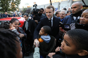 French President Emmanuel Macron shakes hands as he arrives for a visit focused on the theme of urban planing in Clichy-sous-Bois