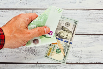 Person changing 50 euros to 100 dollars