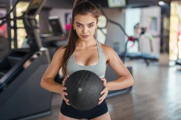 Confident sportswoman posing with ball