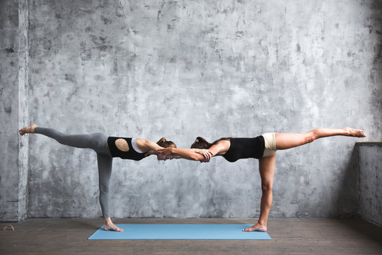 Yoga. Two young women practicing yoga poses.