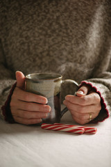 Person holding a hot beverage with peppermint sticks.