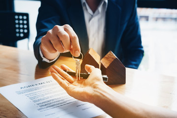 Real estate agents agree to buy a home and give keys to clients at their agency's offices. Concept agreement