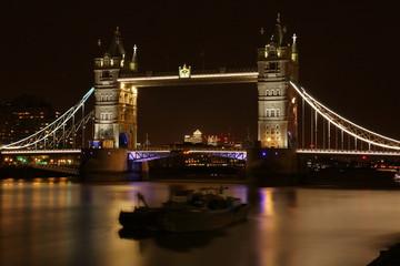 Most Tower Bridge w Londynie, Wielka Brytania, oświetlony kolorowo nocą, na Tamizie dwie niewyraźnie łodzie, barki, długie naświetlanie