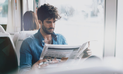 Young freelancer male reading a newspaper while sitting in a city tramway beside a window. Bearded IT specialist with dark hair wearing light blue shirt going to the office by a public transport.