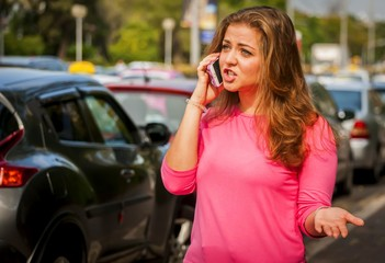 Cute Caucasian young woman talking on a phone in the street. Phone conversation stock image.