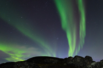 The Aurora in the night sky above the hills.