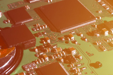 A toned macro image of a computer board with many small technological elements. Extremely shallow depth of field. Abstract technological background