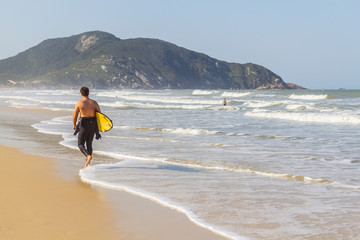 Surfer in Costao do Santinho beach