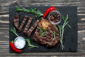 Beef steak with herbs and spices on black slate over wooden background