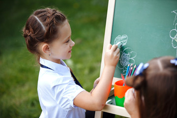 Beautiful girls, school girls in the form of the Park draws on the blackboard