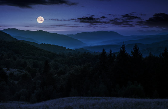 full moon rise above forested mountain at night. gorgeous Carpathian nature scenery