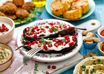 Baked eggplant with yogurt sauce sprinkled with pomegranate fruit and fresh herbs. Healthy and delicious vegetarian meal