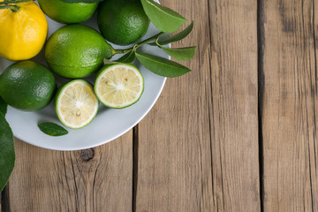 lemon and limes with leaves on a white plate on a wooden background