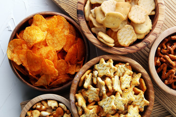 Salty snacks. Pretzels, chips, crackers in wooden bowls.