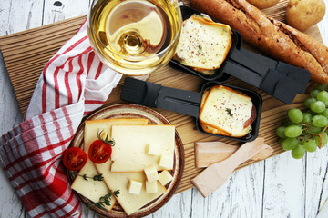 Aluminium Prints Picnic Delicious traditional Swiss melted raclette cheese on diced boiled or baked potato served in individual skillets.