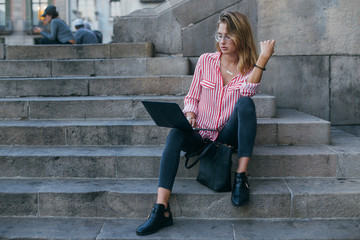 Pretty young woman or student girl sits or rests on steps of office building or university, works on laptop, browses internet for online shopping or business projects, concept freelance or startup