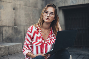 Portrait of casual, fashionable and trendy dressed young millennial woman typing on keyboard or working remotely outdoors, sitting on steps of office building or university, concept young