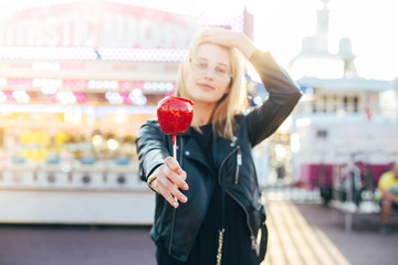 Beautiful young fashion model or lifestyle hipster blogger poses with dreamy and sexy look on her face, sunshine flare in hair, holds holiday candy caramel red apple at amusement park or fair