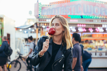Cute, young female in cool black leather jacket and prescription glasses smiling kissing face expression, holds big red candy toffee apple, stands in middle of crowd in amusement carnival park or fair
