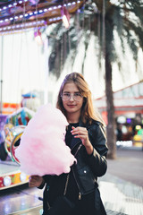 Beautiful young woman or girl stands in middle of country fair carnival, enjoys holiday food, festival pink sugar candy cotton or floss, in front of attraction ride on summer break date or day out