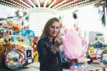 Beautiful young model or attractive woman stands in middle of country fair or carnival, enjoys typical holiday food, festival pink sugar candy cotton or floss, in front of attraction ride on date