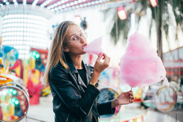 Cute and pretty young girl or student, eats and poses with sugar pink candy cotton, wears leather jacket in line for attraction ride or rollercoaster on town festival, happy times in summer