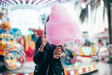 Beautiful model or cute and pretty student woman holds out guilty pleasure, huge pink cotton candy, eats with appetite with fingers, at festival or carnival during summer vacation trip