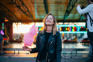 Happy and smiling young woman in cool trendy outfit, hipster or fashion model, enjoys vacations or holidays at amusement park or carnival fair, holds up in sunset light huge pink cotton candy