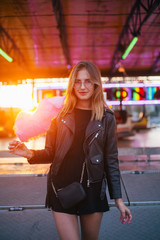 Happy and smiling young woman in cool trendy outfit, hipster or fashion model, enjoys vacations or holidays at amusement park or carnival fair, holds up in sunset pink cotton candy and looks in camera