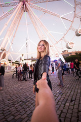 POV shot of boyfriend holding his girlfriend, attractive young blonde woman by hand in front of ferris wheel at amusement park or carnival or festival, enjoying romantic date together, relationship