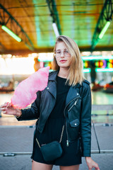 Trendy, natural beauty blonde woman looks into camera, stands next to attraction ride with neon lights at amusement park, holds pink cotton candy and smiles, sexy attractive blogger or hipster student