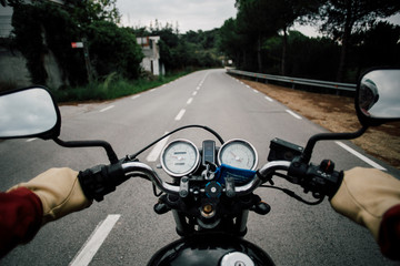 POV from drivers point of view of motorcycle handlebar with speedometer and rear view windows, driving on quiet empty mountain road, driver wears leather gloves and steers confidently