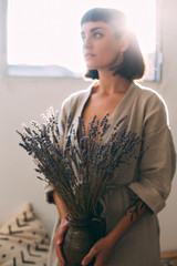 Creative sensual home interior designer or florist artist holds vase with dry lavender flowers, beautiful woman with arm tattoos looks to side with sunshine flare in her hair, hobby or occupation