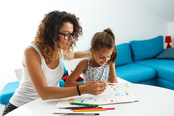 Mother teach her daughter to draw.They sitting at the table in living room