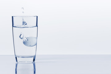 A soluble tablet dropped in a glass of water over white background