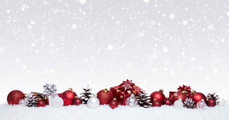 White and red christmas balls with xmas presents in a row isolated on snow, Christmas banner
