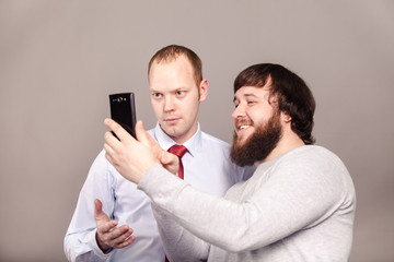 Two smiling colleagues taking the picture to them self, happy friends taking selfie with telephone camera on dark background