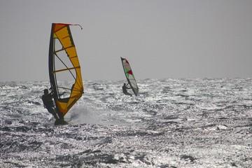 Windsurfers on choppy sea against sun