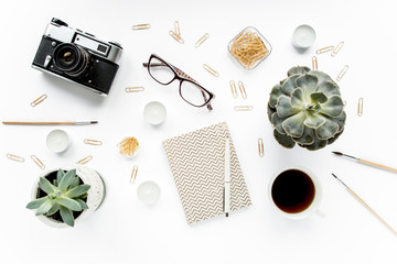 desk workspace with succulent, retro camera, coffee, diary, glasses and golden clips on white background. flat lay, top view