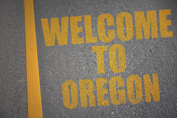 asphalt road with text welcome to oregon near yellow line.