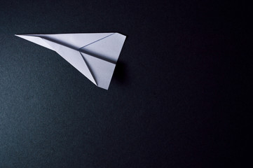 origami plane on dark background pointing to left