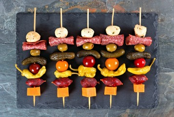 Spoed Fotobehang Voorgerecht Skewer appetizers with cheese, meat and pickles above view on a slate server