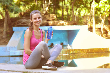 Young sporty woman sitting by the water with a bottle of mineral water in her hand
