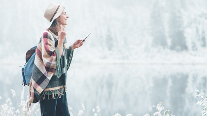 Smiling woman listening music with her mobile phone in first snow. Traveling among stunning winter landscape. Vacations in mountain wilderness. Wanderlust and boho style