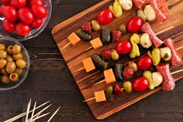 Skewer appetizers with cheese, meat and pickles overhead table scene with wooden background